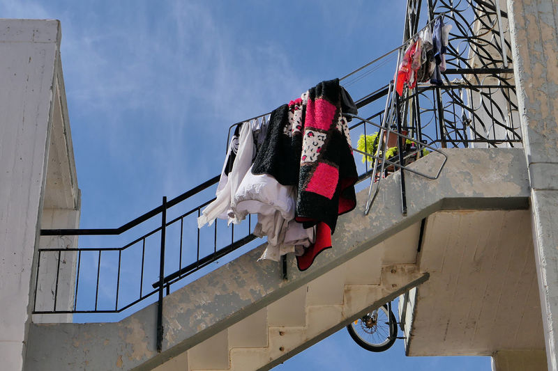 Low angle view of clothes drying on railing against sky