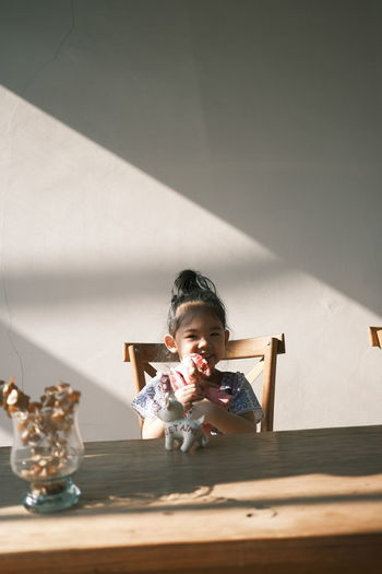 Boy sitting on table against wall