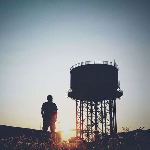 Low angle view of silhouette man standing by water tower against clear sky