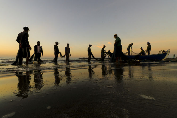 Men standing on shore while fishing in sea against sky during sunset