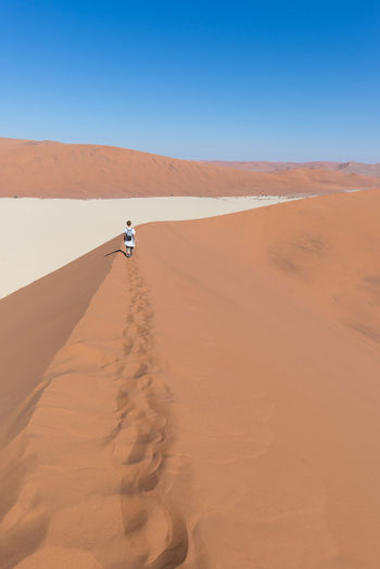 High Angle View Of Woman Walking On Sand Dune In Desert Against Clear Blue Sky