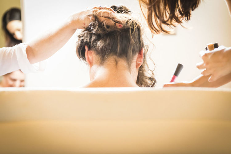 Hairdressers applying make-up of woman body in salon