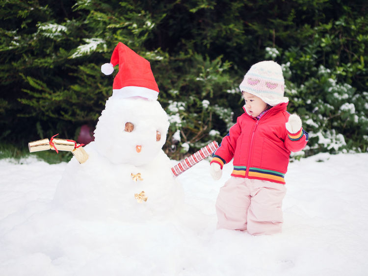White Christmas Asian Baby Girl Baby Girl Celebration Childhood Christmas Christmas Decoration Christmas Tree Cold Temperature Day Full Length Happiness One Person Outdoors People Red Smiling Snowman Tree Warm Clothing
