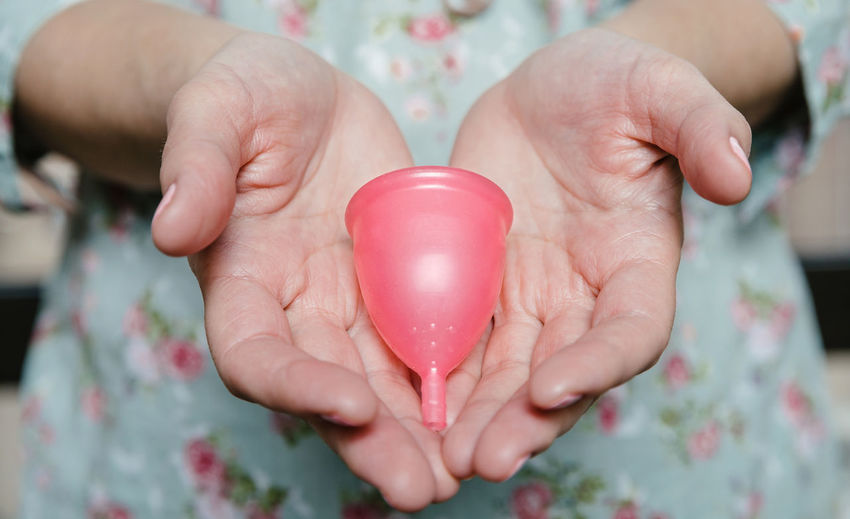 Midsection of woman holding menstrual cup