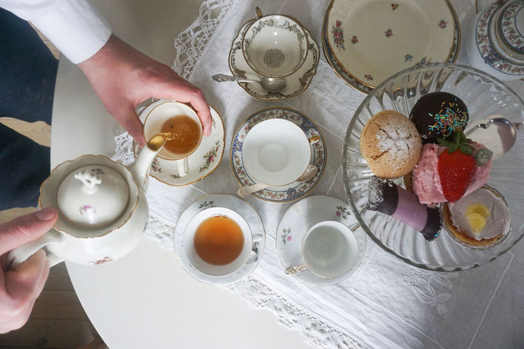 tea time Tea - Hot Drink Tea Time Pouring Tea Human Body Part Human Hand Table Food Food And Drink Cake Cakes Dessert Desserts Cakestand Tart - Dessert Variation Variety Choice White Background Human Hand Table High Angle View Close-up Tea Pastry