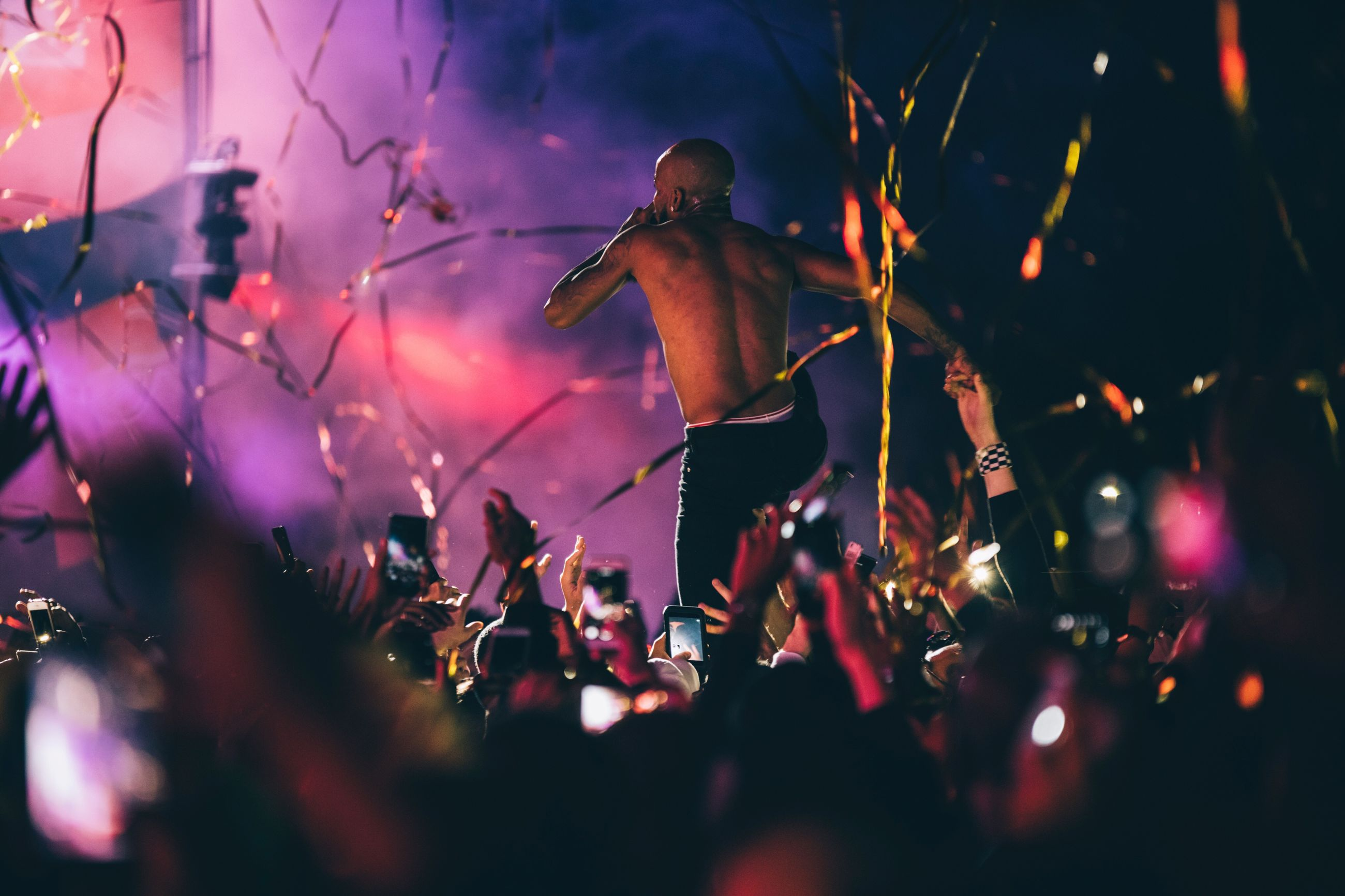 enjoyment, event, fun, large group of people, night, celebration, nightlife, selective focus, crowd, performance, excitement, music, arts culture and entertainment, togetherness, leisure activity, audience, popular music concert, outdoors, illuminated, youth culture, real people, close-up, people