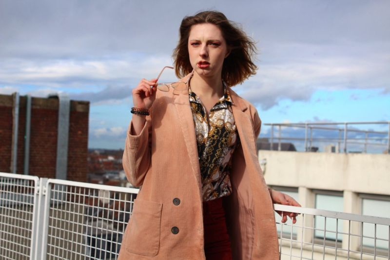 Portrait of beautiful young woman wearing overcoat in city