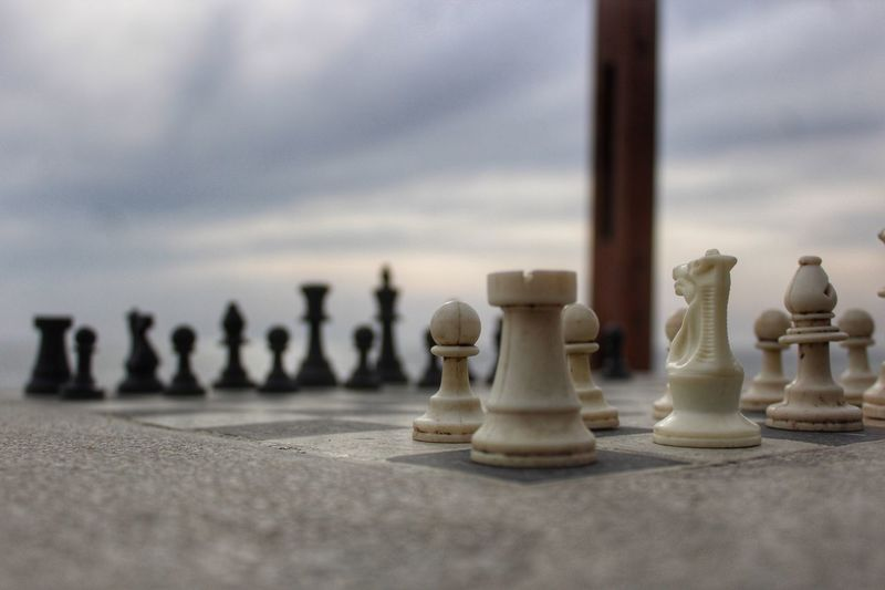 Close-up of chess pieces against sky