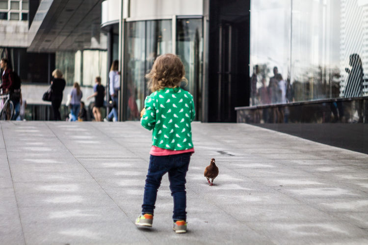 Architecture Casual Clothing Child Childhood City Day Focus On Foreground Hair Incidental People Innocence Jeans Motion Offspring on the move One Person Outdoors Rear View Street Transportation Walking