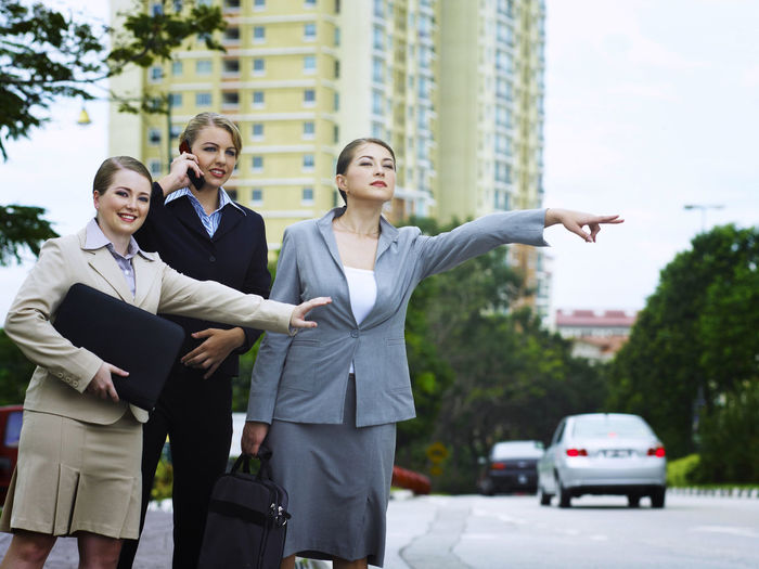 Businesswoman with colleagues hitchhiking on road