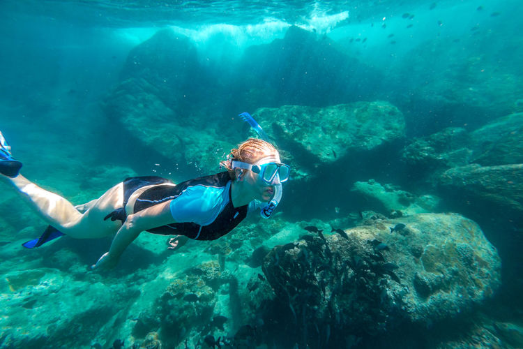 Woman snorkeling over rocks undersea
