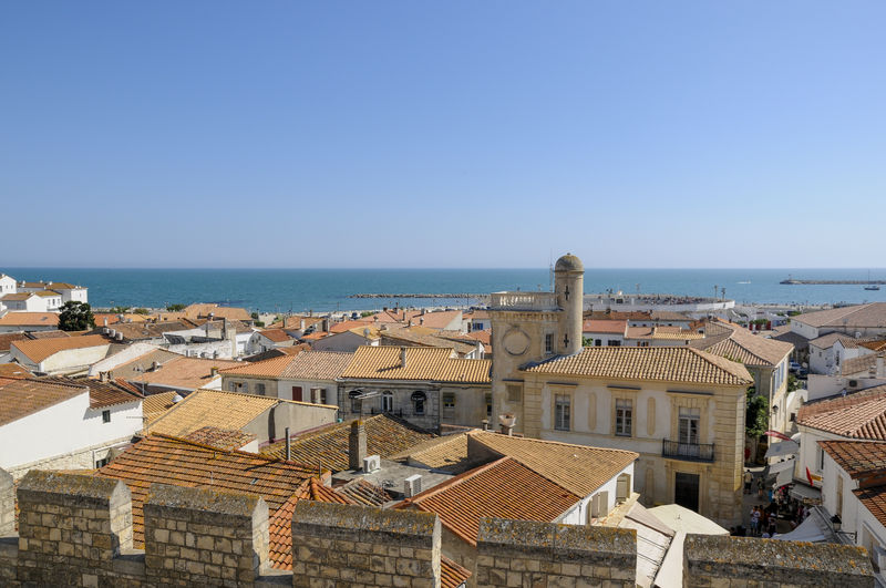 High angle view of buildings by sea against clear sky
