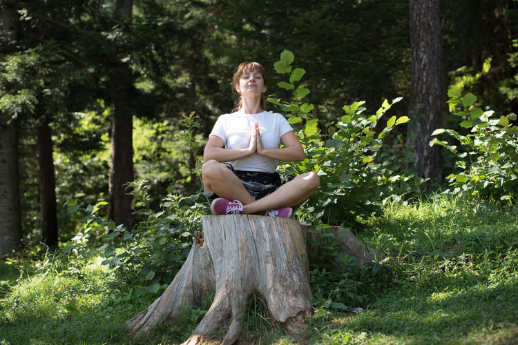 Full length of young woman doing yoga on tree stump at forest