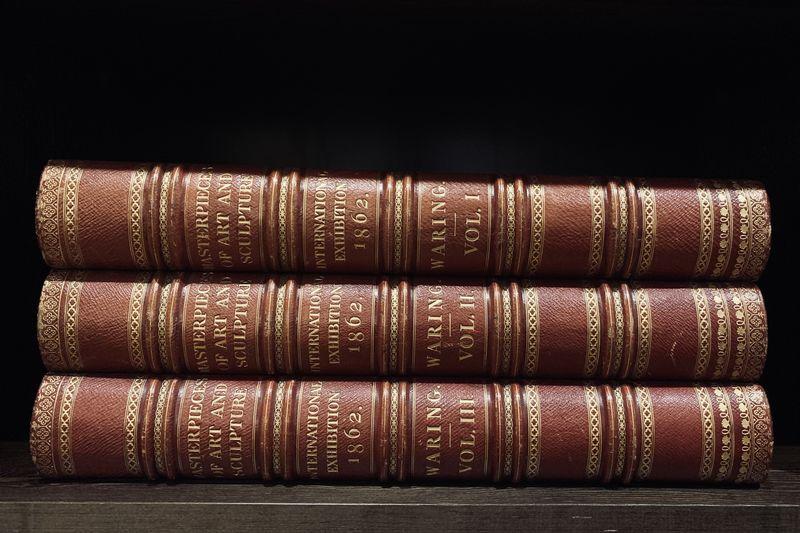 Close-up of books on shelf against black background