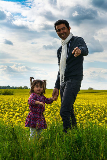 Portrait of father and daughter standing on field against cloudy sky