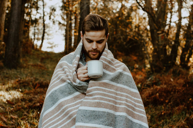 Young man wrapped in blanket having coffee in forest