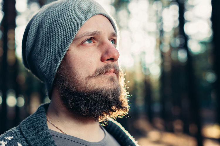 Thoughtful man wearing knit hat in forest