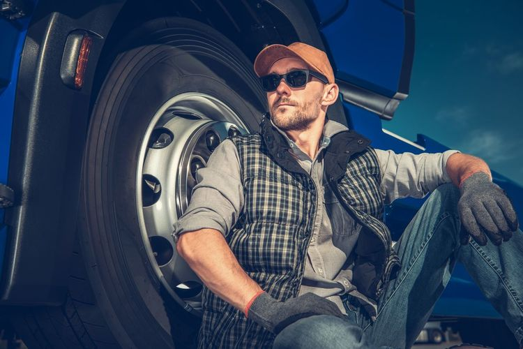 Relaxed Caucasian Truck Driver Seating on the Ground and Support His Back on the Semi Truck Wheel. Trucker Truck Driver Driving Industry Automotive Transportation Transport Men Job Relaxed Relaxing Satisfied  Labor Industrial Outdoors Caucasian