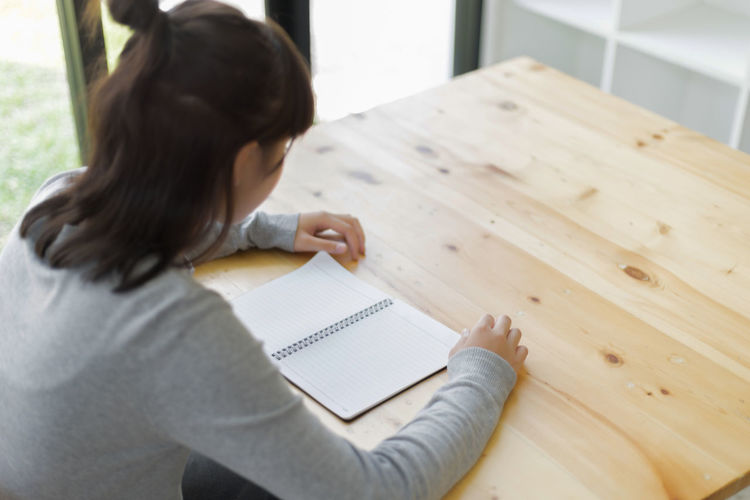 Teenage girl with blank spiral notebook sitting at table