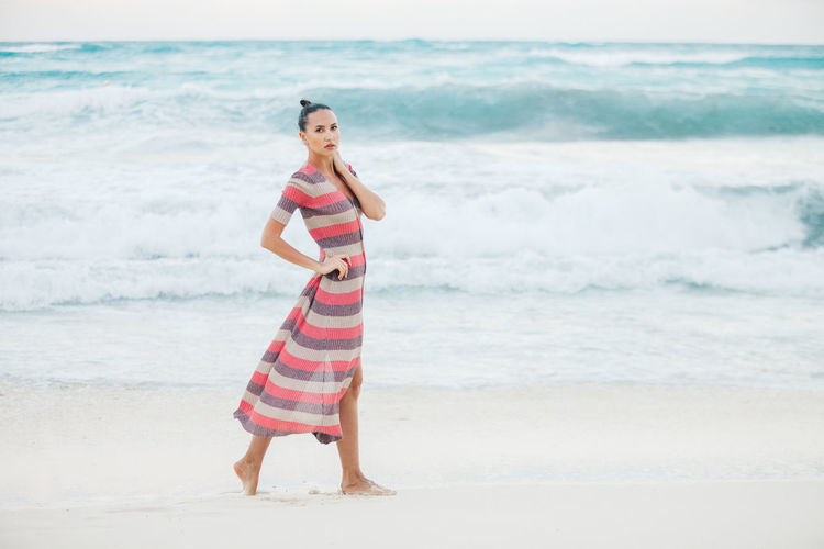 Full length portrait of young woman standing at beach