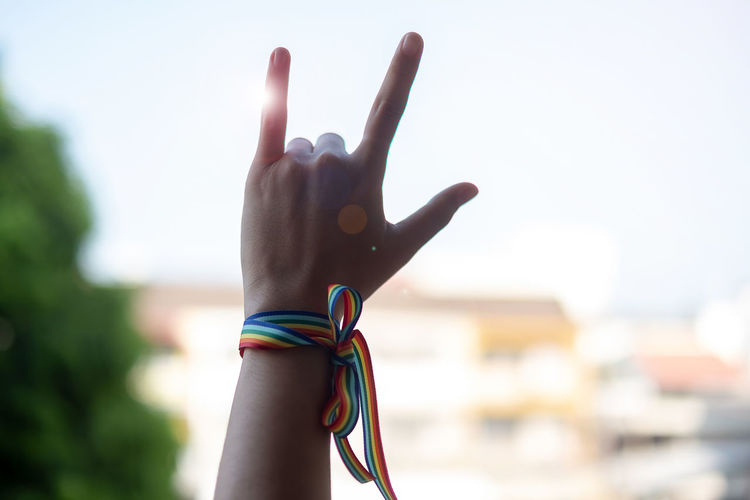 Low angle view of hand wearing rainbow colored wristband gesturing against sky