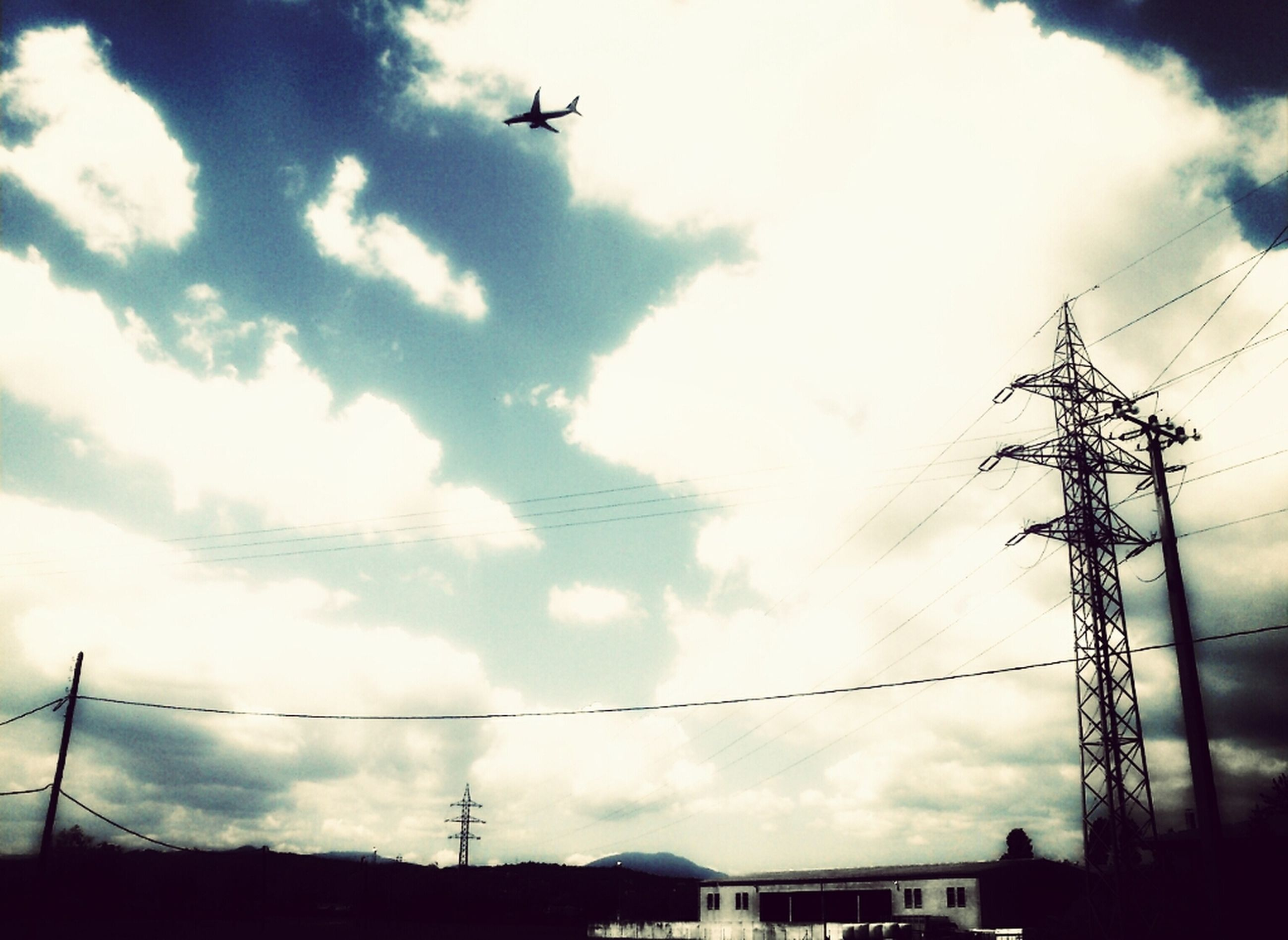 sky, low angle view, power line, cloud - sky, transportation, cloudy, electricity, electricity pylon, building exterior, cloud, mode of transport, fuel and power generation, technology, airplane, cable, power supply, connection, built structure, silhouette, street light