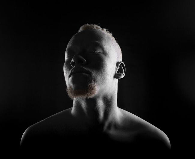 Close-Up Of Shirtless Man With Eyes Closed Against Black Background