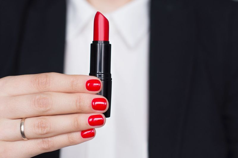 Young woman in white shirt and black suit holding red lipstick Lipstick Cosmetics Beauty Product Makeup Red Lipstick Woman Hands Business Woman Strongwoman Office Power Classical Style Boss Stylish Female Red Hand Nail Polish One Person Human Body Part Nail Close-up Red Nail Polish Adult Holding Women Fashion Manicure