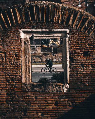 Man and bicycle against brick wall of building