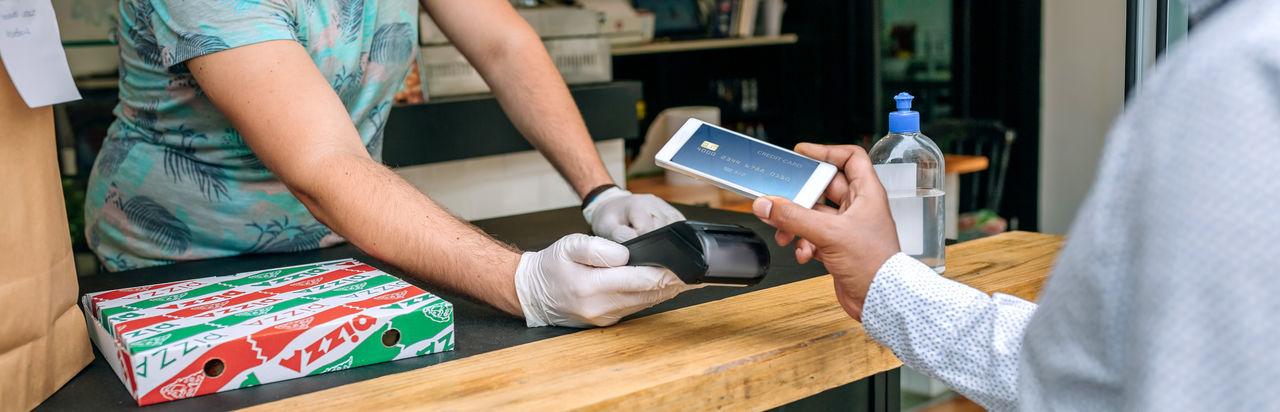 Man making contactless payment through smart phone at restaurant