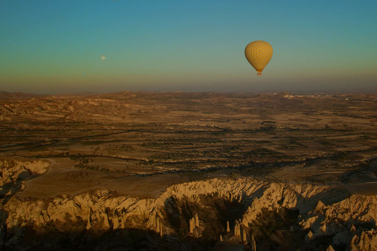 Hot air balloon flying over cappadocia against clear sky during sunset