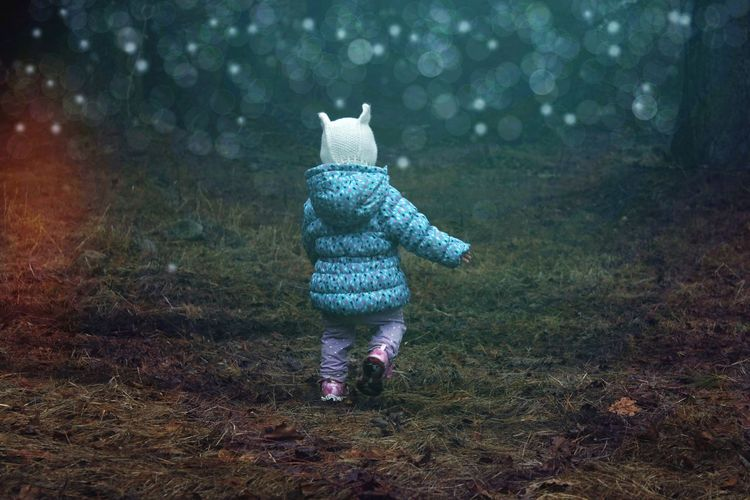 Rear view of baby girl wearing warm clothing walking on field in forest