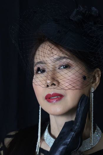 Close-up portrait of mature woman wearing veil against black background