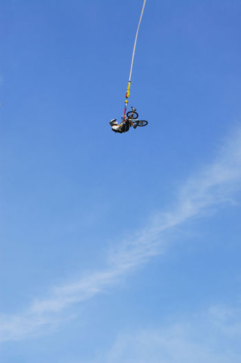 Low angle view of man with bicycle hanging against blue sky