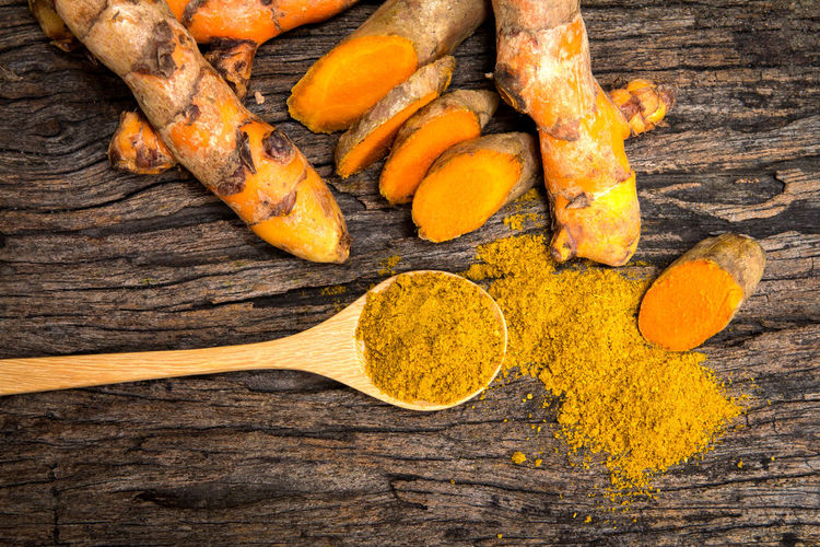 the turmeric powder in spoon and roots on wooden plate Curcuma Curcuma Root Curcumin Directly Above Food Food And Drink Freshness Healthy Eating High Angle View Ingredient No People Orange Color Preparation  Spice Studio Shot Turmeric  Vegetable Wellbeing Wood - Material Yellow