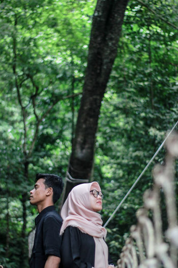 Couple standing back to back in forest