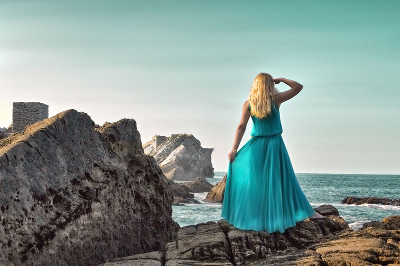 Rear view of woman standing on cliff by sea against sky