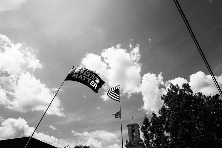 Low angle view of flag on street against sky