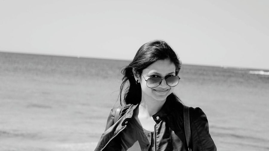 Portrait of smiling young woman standing at beach against clear sky