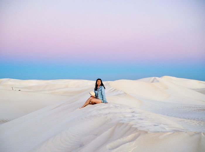 Full length of woman sitting on sand dune against sky during sunset