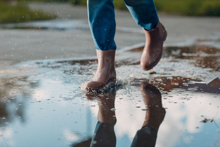 Low section of man with reflection in puddle
