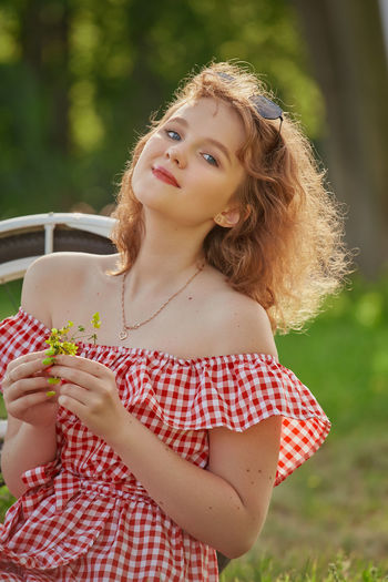 Portrait of beautiful woman holding camera while standing outdoors