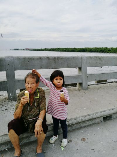Grandmother and granddaughter eating ice cream on bridge against sky during sunset