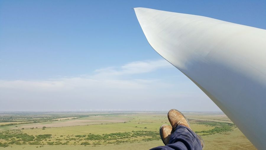 Low section of person beside part of wind turbine against cloudy sky
