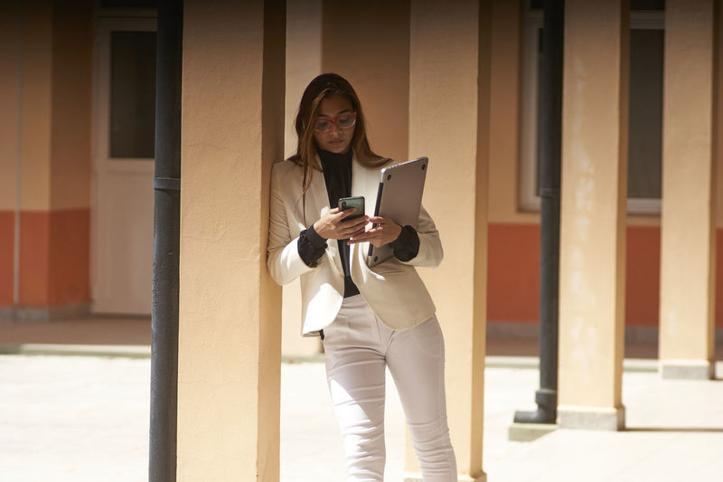 Full length of woman using phone while standing on building