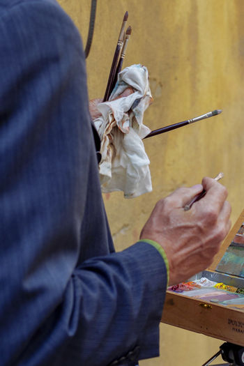 Midsection of man holding paintbrushes