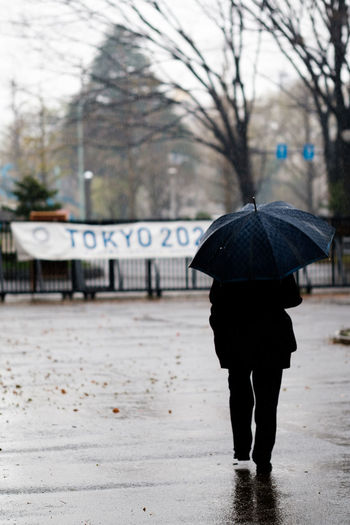 Tokyo, Japan. Alone. Architecture Below City Day Focus On Foreground Full Length Lifestyles Men Nature One Person Outdoors People Protection Rain Rainy Season Real People Rear View Tree Under Walking Water Weather Wet