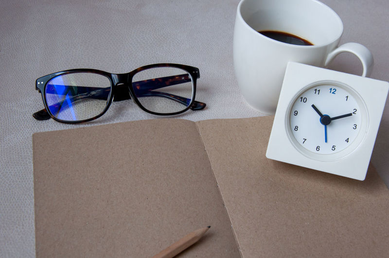 High angle view of brown paper with clock and cup by eyeglasses