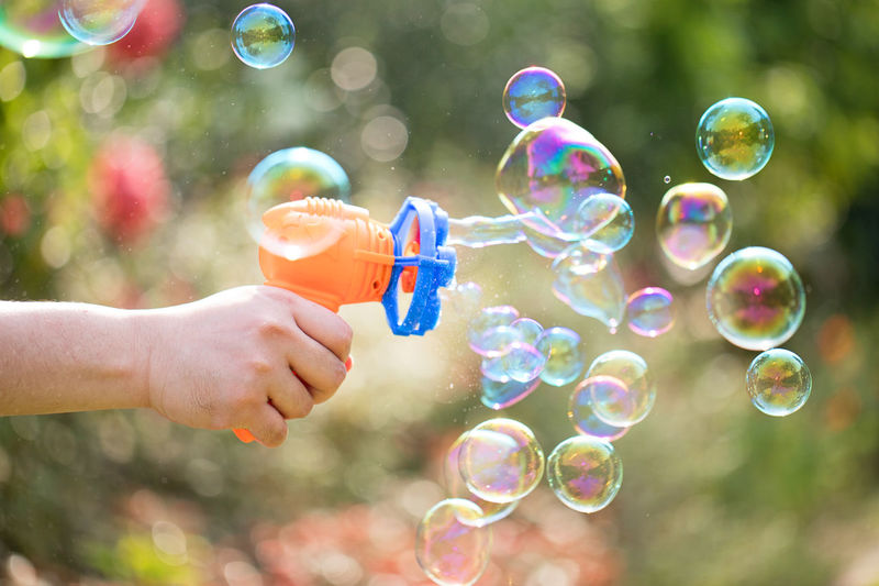 Bubbles Motion Blowing Bubble Bubble Wand Childhood Day Double Rainbow Enjoyment Focus On Foreground Fragility Fun Holding Human Body Part Hummingbird Leisure Activity Lifestyles Lightweight Mid-air Motion One Person Outdoors Rainbow Real People Soap Sud Spectrum Transparent