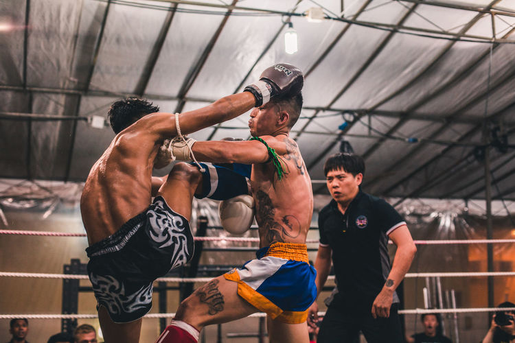 Precision blows Sport Men Muscular Build Determination Vitality Effort Boxing Glove Shirtless Young Adult Competition Real People Boxing - Sport Strength Healthy Lifestyle Athlete Young Men Exercising Lifestyles Muay Thai Fighting Fitness Punching
